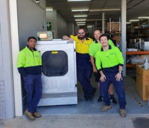 A group of men standing around the HUBSCRUB Machine